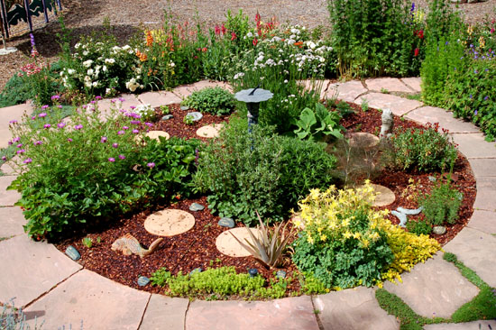 Herbs join flowers, ceramic fish, and a sun-dial in this garden in Santa Fe, NM