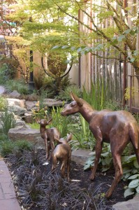Alert to the urban sounds just beyond the fence, bronze deer bring a welcome reminder of the natural world to a pocket garden in Portland, OR.